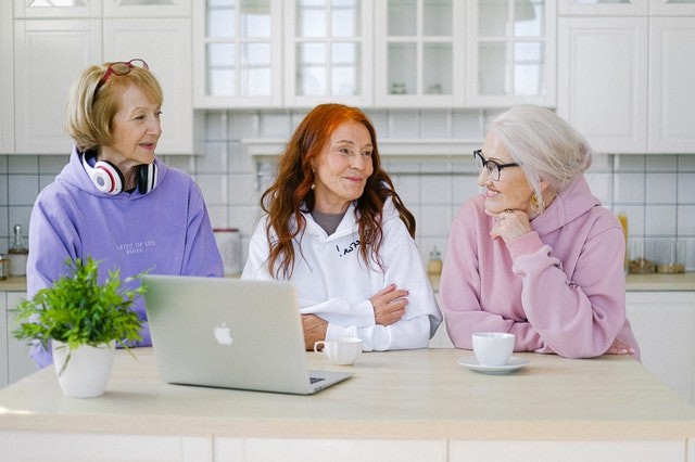 Three elderly ladies looking at laptop and searching for the best cities in Florida for senior homebuyers