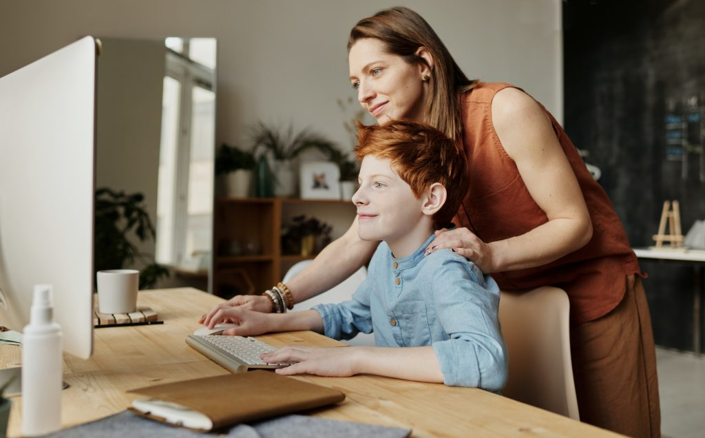 woman and a child doing a research about family relocation to Hurst on the computer