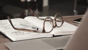 an image of eyeglasses with gray frames on top of a notebook